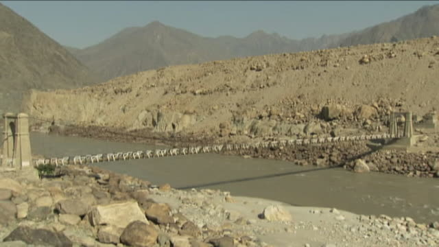A footbridge crosses the Indus River in Pakistan. Available in HD.