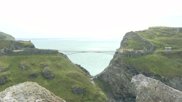 footbridge linking tintagel castle to the mainland in cornwall - crossing stock videos & royalty-free footage