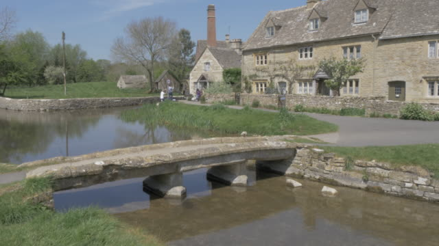 vídeos y material grabado en eventos de stock de footbridge over river eye toward old mill museum in lower slaughter, cotswolds, gloucestershire, england, united kingdom, europe - cotswolds