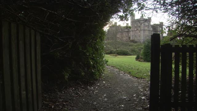 ms, footpath in park, stone castle in distance, oban, scotland, england - cultura britannica video stock e b–roll