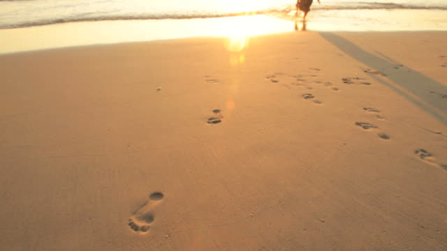 CU Footprints on beach, boy (4-5) and girl (6-7) running in background
