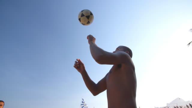 footvolley player leaps up to head soccer ball over net on copacabana beach - internationaler fußball stock-videos und b-roll-filmmaterial