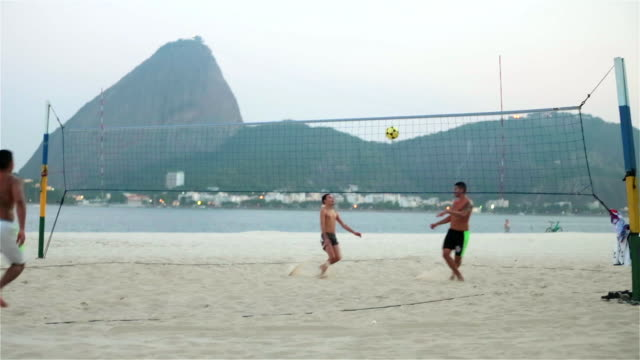 footvolley teammates serve and volley soccer ball back and forth over net on brazilian beach - internationaler fußball stock-videos und b-roll-filmmaterial
