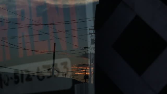 For rent sign reflection from window with sunset