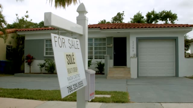 for sale sign is seen in front of a home as the national association of realtors released a report showing that home sales dropped in december of... - 不動産の看板点の映像素材/bロール