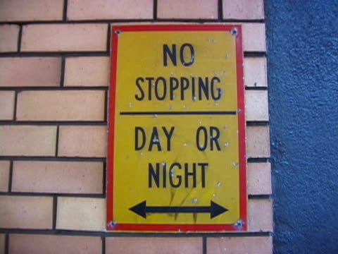 """forbidden: """"no stopping"""" road sign on brick wall - forbidden stock videos & royalty-free footage"""