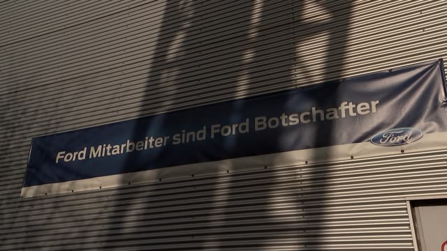 ford factory in cologne general views ext wide shot factory / lorry's away / people along / ford sign / ford badge on car / entrance to factory... - ford marca di veicoli video stock e b–roll