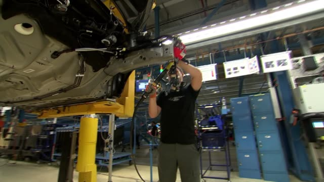 ford factory in cologne general views workers along production line / workers under cars / various of car assembly process / tyres put onto cars - ford motor company stock videos & royalty-free footage