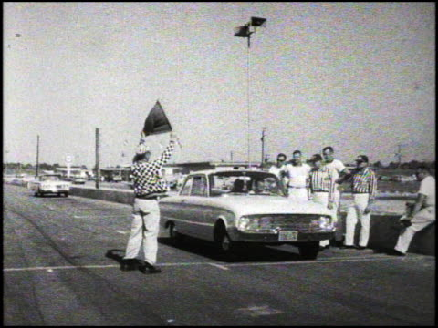 ford falcon at the starting line for the 1960 pure oil economy trials; nascar official waves the starting flag and...nothing. the falcon waits and... - 1960年点の映像素材/bロール