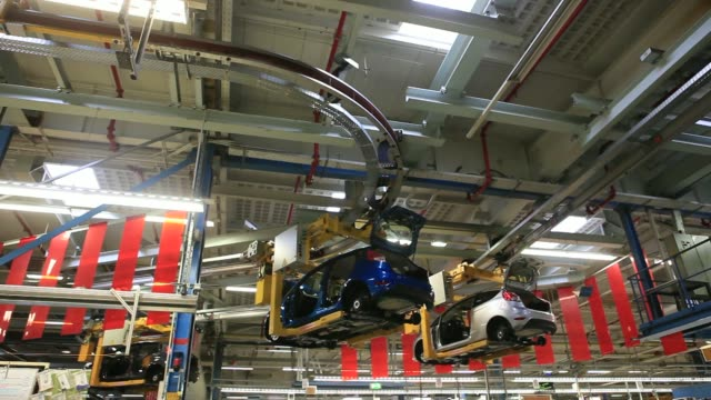 ford fiesta automobiles are carried on a overhead conveyor at the ford motor co factory in cologne germany on friday march 21 a ford car is... - ford motor company stock videos & royalty-free footage
