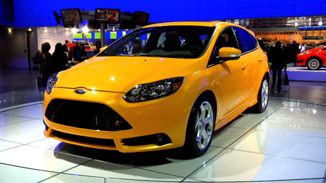 vidéos et rushes de ford oval wall logo; front three-quarter driver side view of ford focus st / rear end 2013 ford focus st montage at cobo center on january 24, 2013... - cadrage aux genoux
