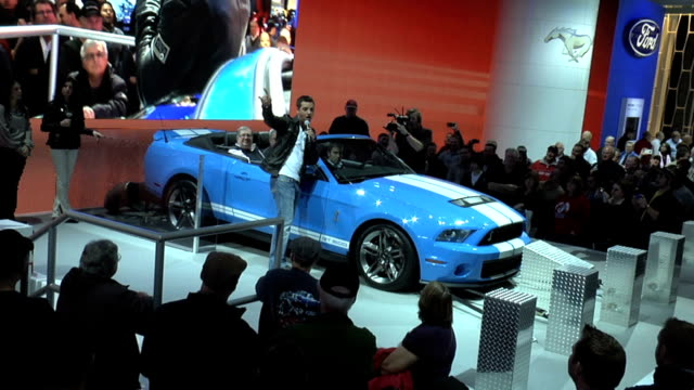 Ford Shelby GT500 on raised stage NARRATOR ON STAGE talks about supercharged V8 producing 550 horsepower Car then accelerates to 140 miles per hour...