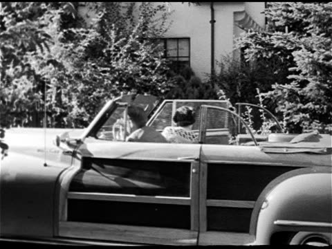 stockvideo's en b-roll-footage met ford sportsman woody convertible pulling up to side curb of yard ms male female couple getting out of parked car walking to house picking up paper... - 1948