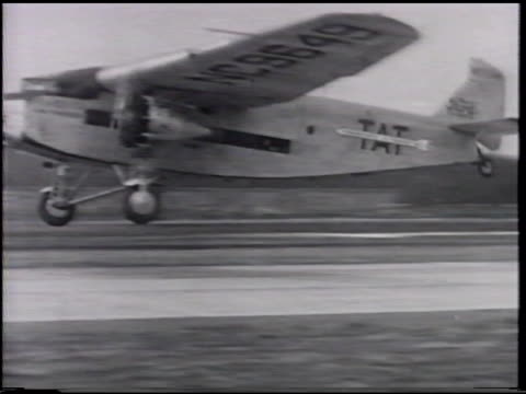 ford trimotor highwing monoplane taking off tat on side vs passengers served by flight attendant helping w/ coat newspaper woman child at window ws... - flugpassagier stock-videos und b-roll-filmmaterial