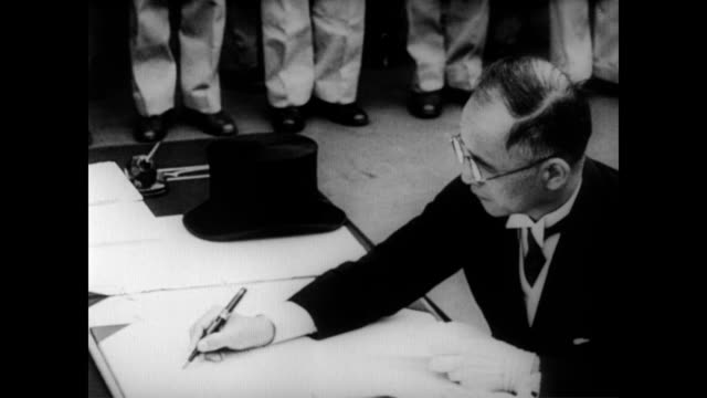 / foreign affairs minister mamoru shigemitsu sits at desk on board uss missouri to sign japanese surrender documents / general douglas macarthur then... - arrendersi video stock e b–roll