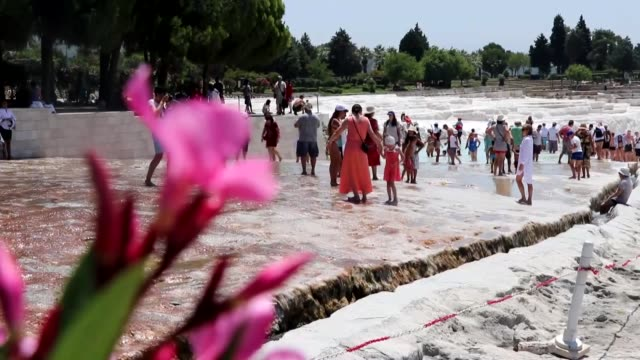 Foreign and local tourists visit Pamukkale a UNESCO World Heritage site in Denizli in the Aegean region of Turkey on July 05 2018 Pamukkale meaning...