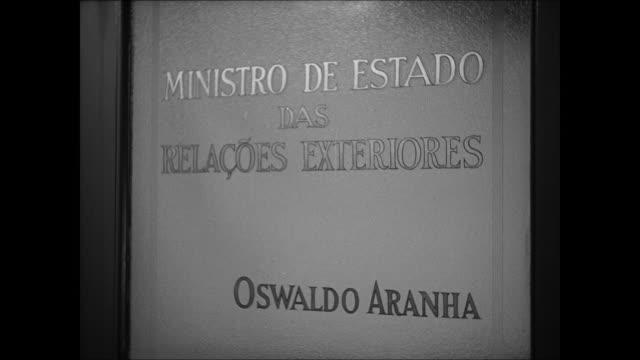 Foreign Office pool FG INT MS Door sign in Spanish 'Minister of State of Foreign Relations Oswaldo Aranha' INT MS Aranha talking w/ Jefferson Caffery...