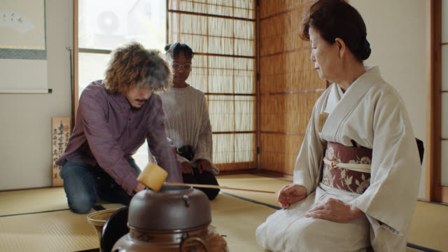 foreign tourist guests observing hostess stirring tea at traditional japanese ceremony - washitsu stock videos and b-roll footage