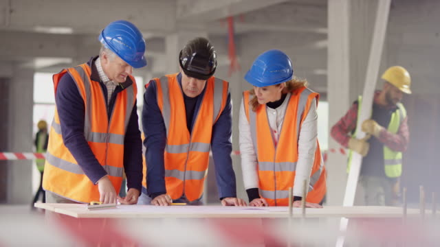 foreman and forewoman talking to a male architect leaning over the construction plans at the building site - caposquadra video stock e b–roll