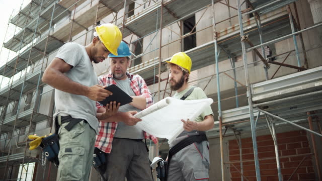 Foreman and his workers holding the digital tablet and the plan and talking about the time line