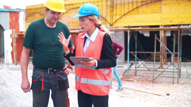 Foreman and manual worker using digital tablet on construction site