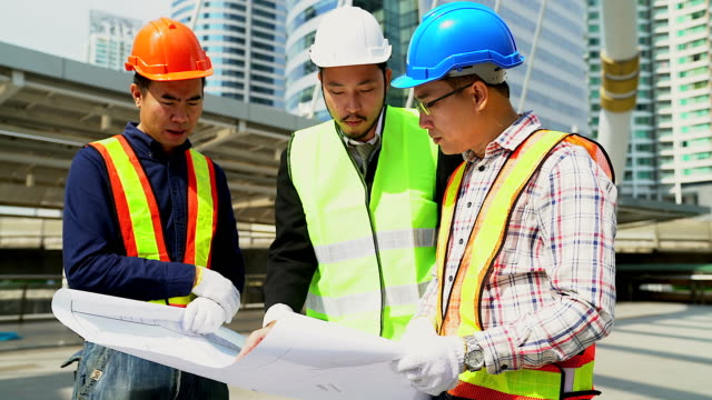 Foreman builder and construction worker discussion with blueprint at construction site.