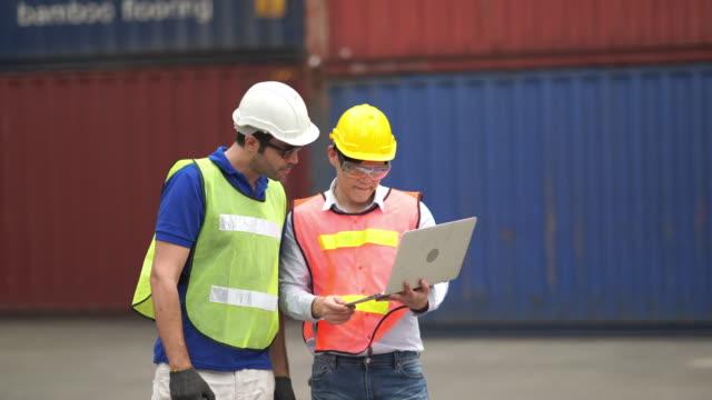 vidéos et rushes de foreman contrôle la boîte de chargement des conteneurs de l'entrepôt de cargo - débardeur