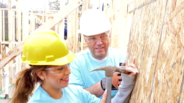 foreman helps young volunteer as they build home for charity - hammer stock videos and b-roll footage