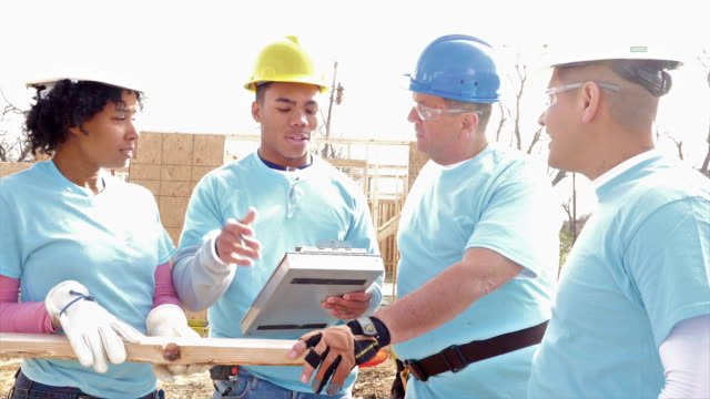 Foreman instructs diverse group of volunteers building home for charity