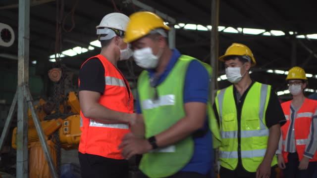 vídeos de stock, filmes e b-roll de foreman é medir os trabalhadores da fábrica de temperatura no local da fábrica. - sob proteção