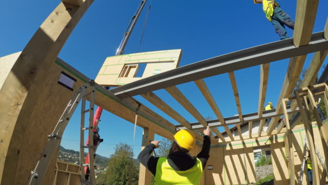 Foreman signaling the worker operating the crane to move a wooden wall for the prefab home