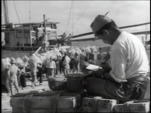 stockvideo's en b-roll-footage met 1938 ws foreman sitting on crate writing in notebook with crowd of workers loading boat under his eye / japan - 1938
