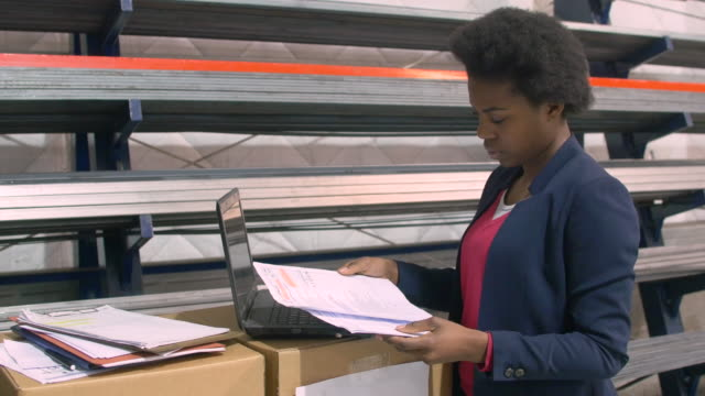 Foreman with documents and laptop in warehouse