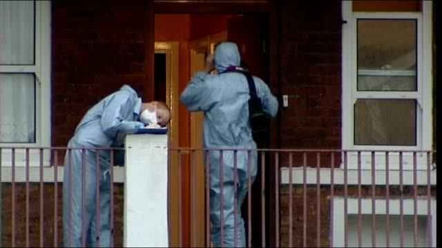 forensic officers at flats one taking notes as another films the crime scene forensic officer in white overalls watching men carry body on stretcher... - pompe funebri video stock e b–roll