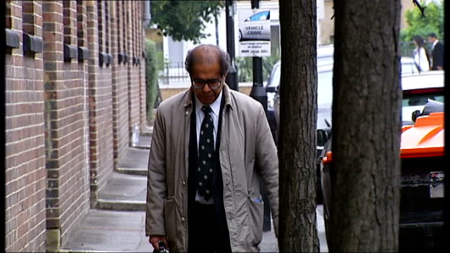forensic pathologist accused of professional incompetence by gmc england ext doctor freddy patel along street and into building - ineptitude stock videos & royalty-free footage