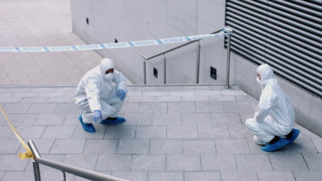 forensic science team working on police investigation site - チョークの跡点の映像素材/bロール