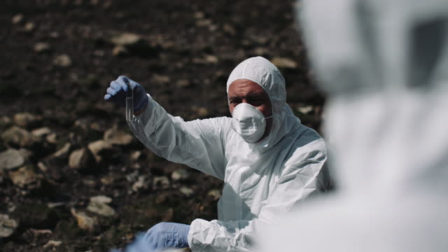 Forensic scientist examining sample at river bank