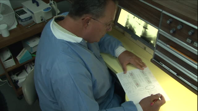 a forensic scientist takes notes as he views dental x-rays. - 法科学点の映像素材/bロール