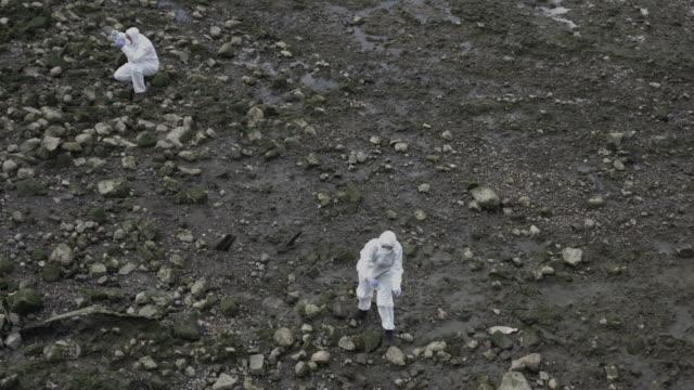 Forensic scientist taking sample at river bank