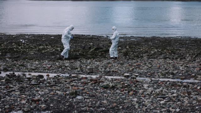 forensic scientist taking sample at river bank - クリーンスーツ点の映像素材/bロール