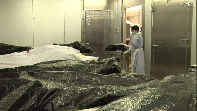 forensic scientists wheel a wrapped up body into a morgue room full of body bags. - forensic science stock videos & royalty-free footage