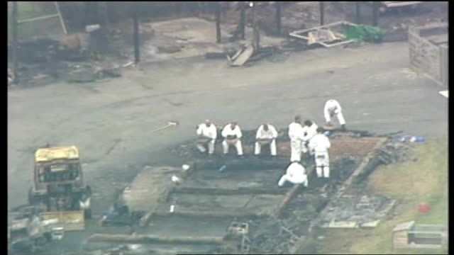 forensic workers sifting through burnt out outbuildings - sifting stock videos and b-roll footage