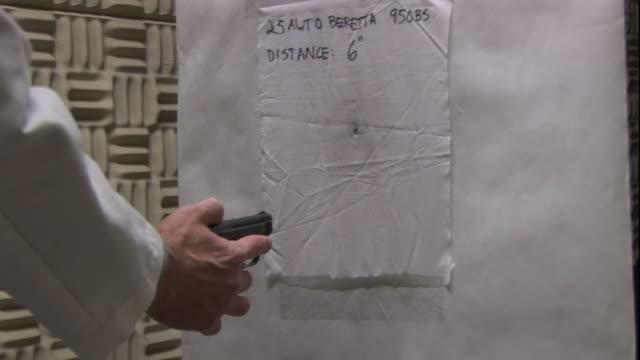 a forensics technician shoots a target at close range. - 法科学点の映像素材/bロール