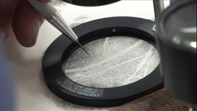 a forensics tool hovers over an enlargement of a fingerprint. - 指紋点の映像素材/bロール