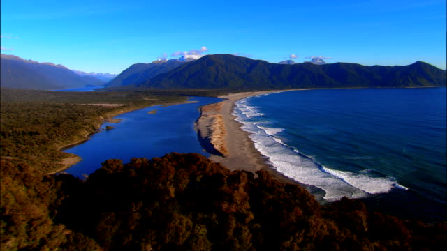 LOW AERIAL, Forest and beach at Martins Bay, Fiordland National Park, New Zealand