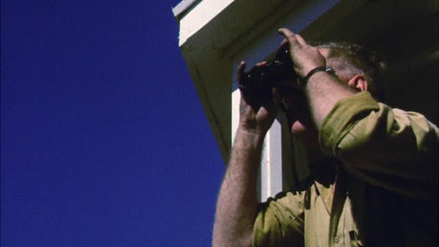 ms forest ranger in tower looking through binoculars - binoculars stock videos & royalty-free footage