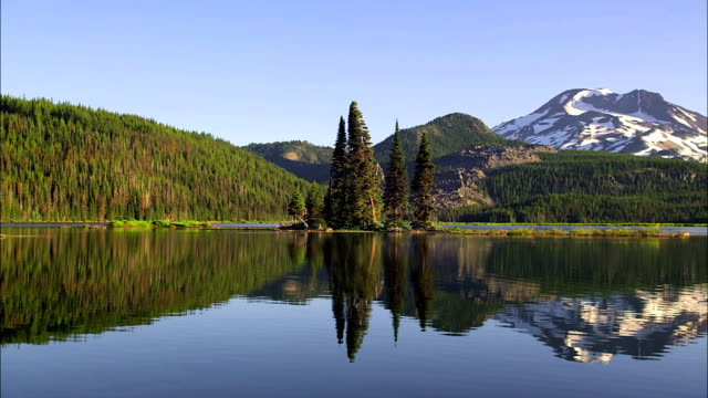 forested hills reflect in sparks lake with three sisters mountain range in background (part of cascade mountain range) near bend, oregon. - cascade range stock videos & royalty-free footage