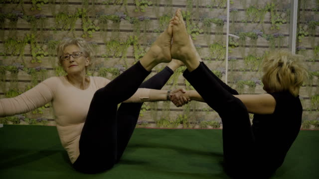 vídeos y material grabado en eventos de stock de para siempre joven y saludable, clase de yoga para personas mayores - equilibrio vida trabajo