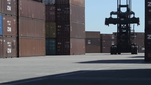 Fork Hoists are used to stack containers in the container yard of the Port of Tampa in Tampa Florida US A fork hoist lifts shipping containers off of...