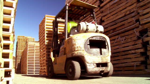 fork lift removes stack of wooden pallets from pallet storage area at pallet repair and manufacturing plant / Fontana, California, USA
